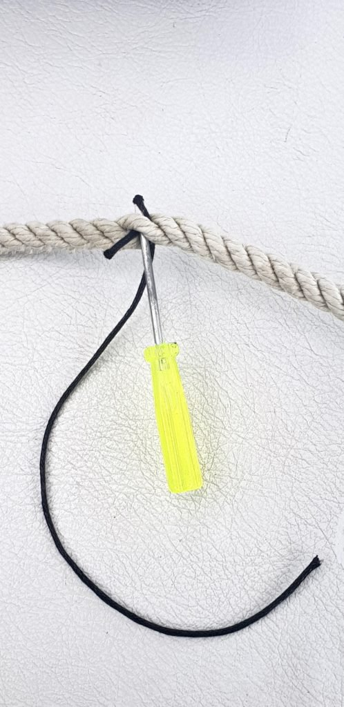 Use a screwdriver to force waxed cord through three-strand cord to make a boat clothesline.